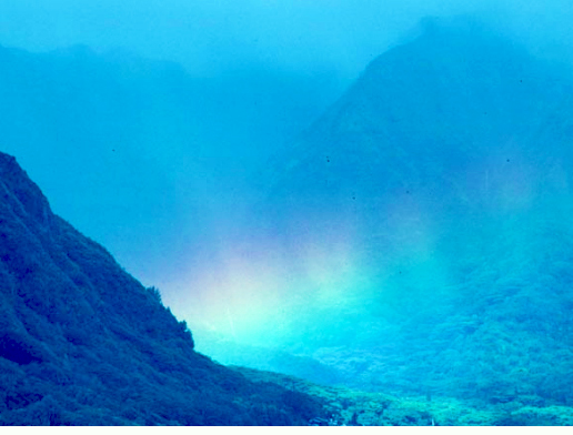Stunning view of a glowing rainbow in the misty mountains